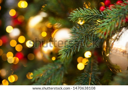 Christmas outdoor background with fir tree branches, decorations and blurred lights on back