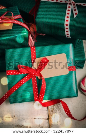 Christmas packages with green paper, red bow and brown label on a white wooden table. Lights effect added.