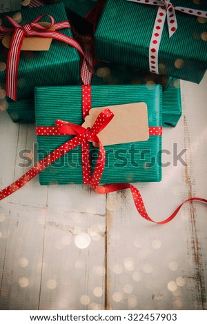 Christmas packages with green paper, red bow and brown label on a white wooden table. Lights effect added