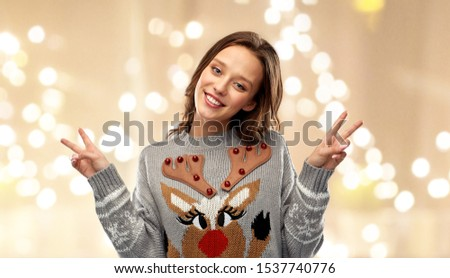 christmas, party and holidays concept - happy young woman wearing ugly sweater with reindeer pattern showing peace over grey background over festive lights background