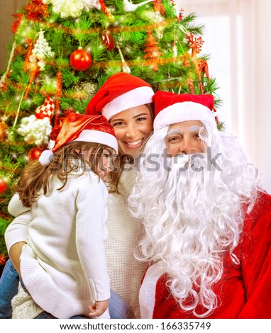 Christmas party, happy family at home celebrating New Year, mother with daughter and Santa claus near Xmas tree, happiness concept