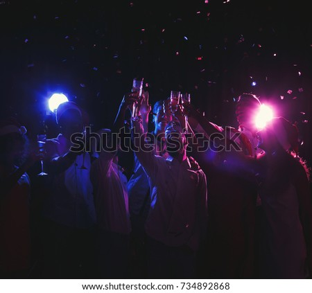 Christmas party time. Young people toasting with champagne flutes. Holidays, celebration and nightlife concept
