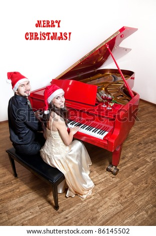 Christmas party with Man and woman in Christmas hats playing the piano and smiling with wine glasses and red rose on the red grand piano. Free space for text