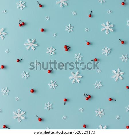 Christmas pattern made of snowflakes and red berries on blue background. Winter concept. Flat lay. #520323190
