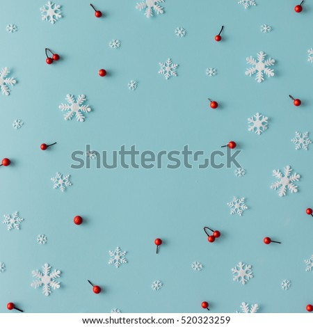Christmas pattern made of snowflakes and red berries on blue background. Winter concept. Flat lay. #520323259