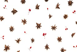 Christmas pattern with anise stars and red berries isolated on white. Flat lay. View from above.