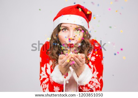 Christmas, people concept - woman in santa suit blowing colourful sequins on background with copy space