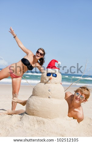 Christmas people on beach with snowman made out of sand wearing sunglasses.