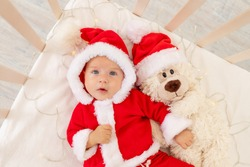Christmas photo of a baby in a Santa costume lying in a crib at home with a toy in a Santa Claus hat, top view, happy new year.