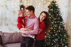 Christmas photo of a happy family around a decorated Christmas tree.
