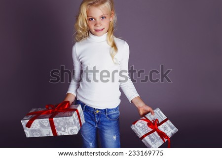 Christmas photo of little cute girl 9 years old wearing Santa hat and holding big present box