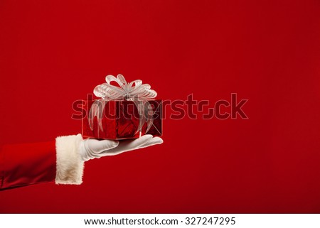 Christmas. Photo of Santa Claus gloved hand with red gift box, on a red background #327247295