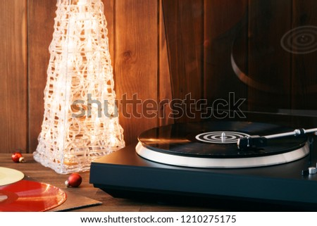 Christmas picture. The rotating moment of a black vinyl record on the turntable, the stylus with a needle falls on vinyl, music on the background of a glowing Christmas tree with red glass balls