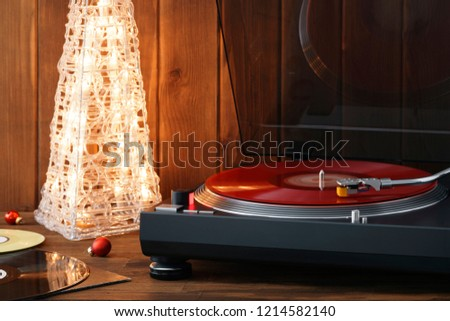 Christmas picture. The rotating moment of a red vinyl record on the turntable, the stylus with a needle falls on vinyl, music on the background of a glowing Christmas tree with red glass balls
