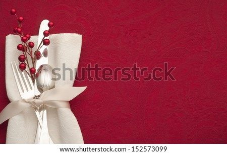 Christmas Place Setting with Sterling Silverware in White Napkin and Ribbon on Red Background with Copy space or Room for Your Text or Words.