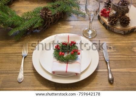Christmas place setting with vintage dishware, silverware and decorations on wooden board. Side view. Christmas wreath as decor. #759642178