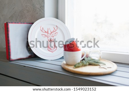 Christmas plate and mugs on the windowsill in the house