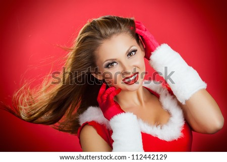 Christmas portrait of a beautiful young woman with bright make-up and developing hair on a red background