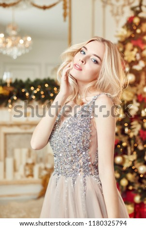 Christmas portrait of a girl in a glittering festive dress on the background of Christmas decor in elegant interior. A woman is preparing to celebrate Christmas and new year