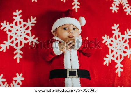 b6215d42c Christmas portrait of adorable newborn baby wearing Santa Claus' outfit,  lying on snowflake blanket