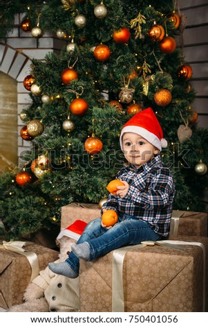 Christmas Portrait Of Happy Smiling Little Boy In Red Santa Hat Sitting On Boxes With Presents