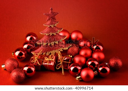 Christmas postcard over red background with sparkle red christmas tree, red globes and shinny red gifts with golden ribbons