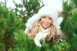 Christmas poster. Young smiling woman with fur white hat, woolen mittens, sweaters in the winter fir forest. Fir branches.