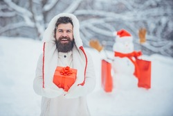 Christmas preparation - funny bearded man with red gift box make snowman. Enjoying nature wintertime. Holly jolly swag Christmas and noel