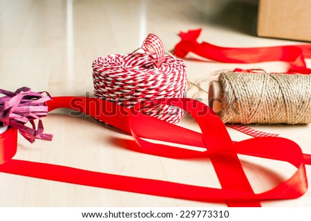 Christmas preparation. Ribbons and accessories for Xmas gift packing on wood floor.