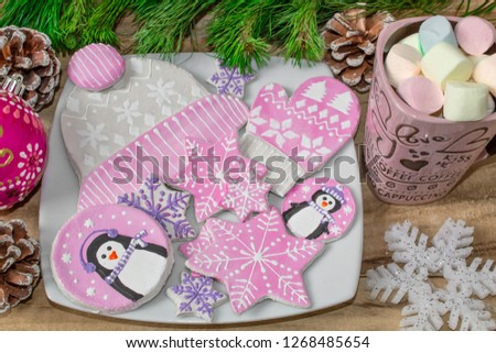 Christmas preparations. Gingerbread, penguins, mittens and hats with asterisks and a mug of marshmallow on a wooden background. Branches of fir and decorations. Festive new year background.