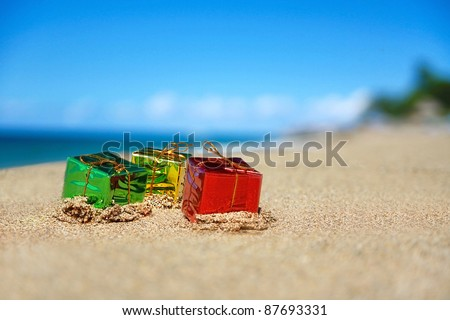 Christmas present boxes on tropical beach
