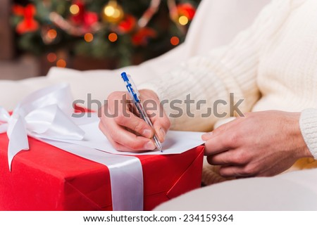 Christmas present. Close-up of man writing Christmas letter with Christmas Tree in the background
