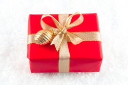 Christmas present packed in red wrapping paper on white snowflakes