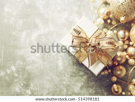 Christmas Present with Gold Ribbon and Gold Christmas Decorations. Rustic Background. Christmas background. Top view. Copy space.