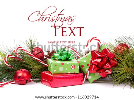 Christmas presents and pine branches with candy canes and ornaments on white background