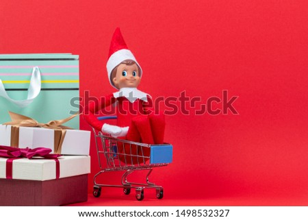 Christmas presents background. Christmas toy elf sitting in mini shopping cart with present box and bags on red background
