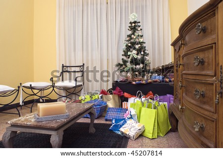 Christmas presents by a tree in a living room.