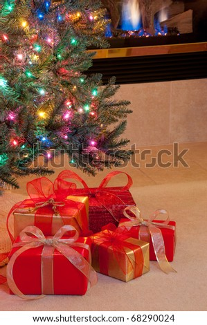 Christmas presents in red and gold under tree by fire