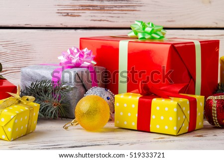 Christmas presents laid on a wooden table background. Gift boxes with bow and ribbon. #519333721