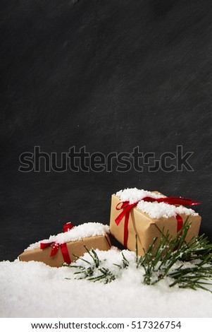 Christmas presents with red ribbon in snow against a blackboard #517326754