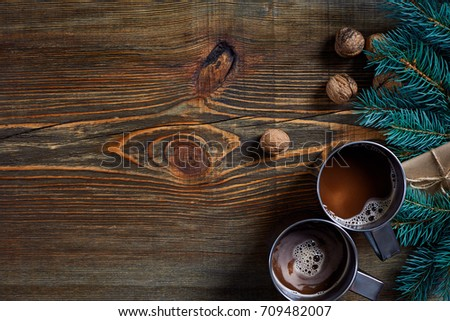 Christmas presents with two cups of cappuccino, nuts, cones and fir branch on wooden background close up #709482007