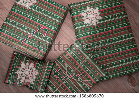 Christmas presents wrapped and stacked in wrapping paper with decoration