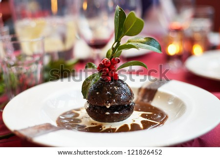 Christmas pudding on a decorated plate and berries