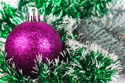 Christmas purple ball on a background of fir branches and tinsel, selective focus, bokeh