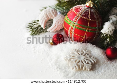 Christmas red ball - decoration on a white background with snow and branch of pine - stock photo