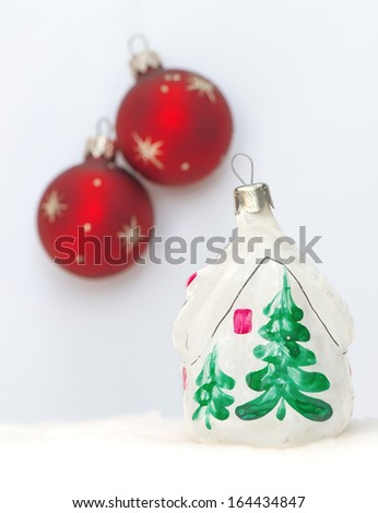 Christmas red balls and toy house on white background