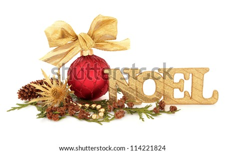 Christmas red bauble decoration with bow with a gold glitter noel sign surrounded by cedar leaf sprigs, pine cones, thistle flower head and bead chain over white background.