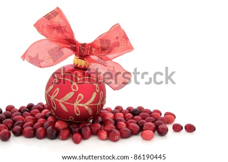 Christmas red bauble with bow and cranberry fruit isolated over white background. - stock photo