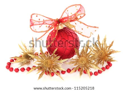 Christmas red bauble with glitter bow with gold thistle flower heads and bead chain decoration over white background.