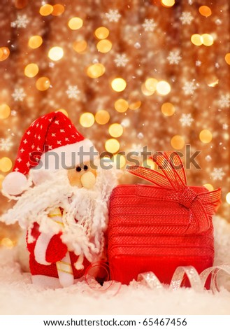 Christmas red gift box present as holiday abstract background card with Christmas tree Santa Claus ornament & defocus lights decoration